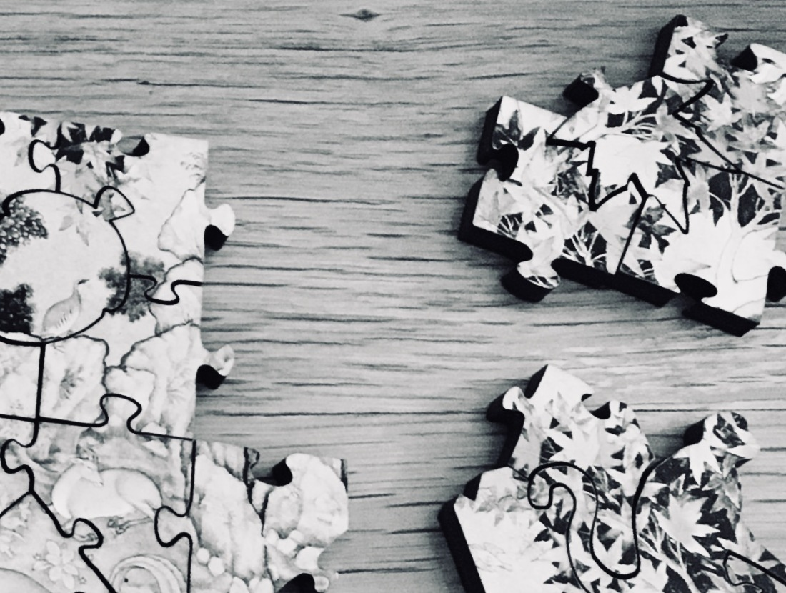 Stylized black and white puzzle pieces on wood background